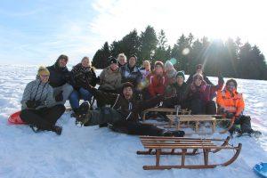 Gruppenfoto im Schnee beim Schlittenfahren